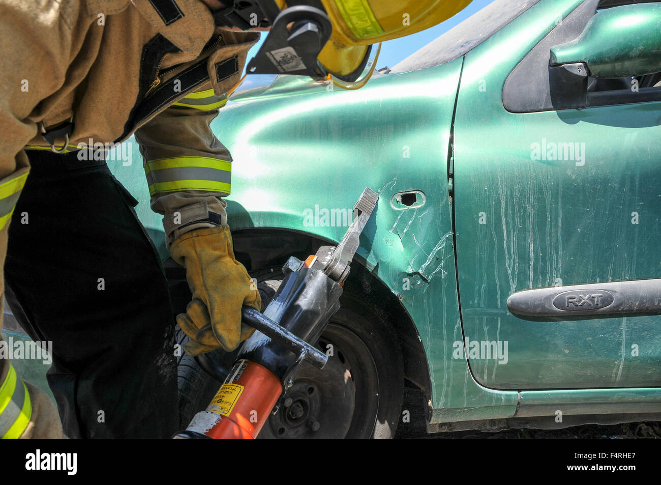 Firefighters use power tools to rescue trapped passengers from a car - Stock Image