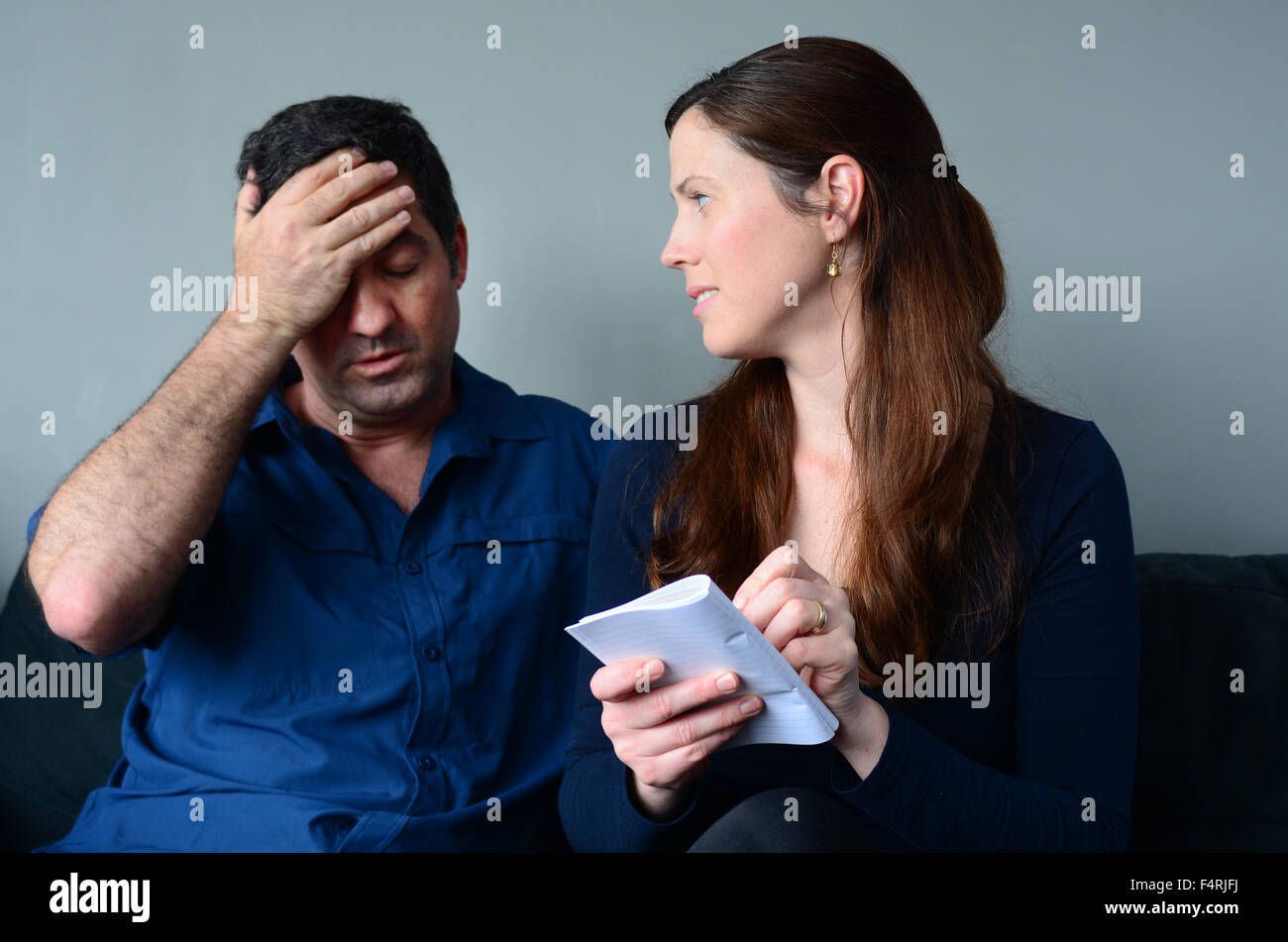 Worried husband and wife  listing expenses in the living room. Spouse relationship concept - Stock Image