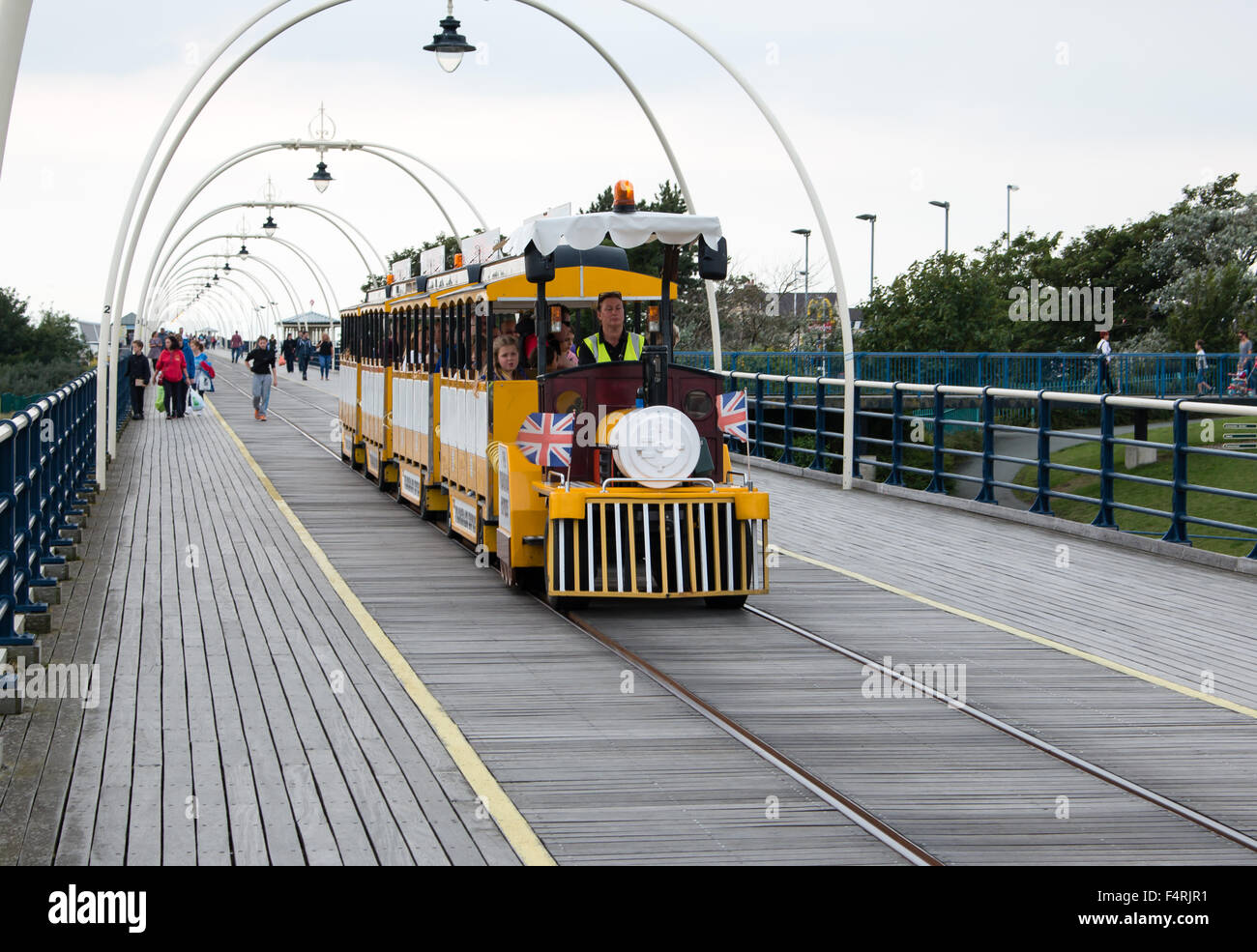 Tourist Tram on Southport Pier. Grey and overcast weather. - Stock Image