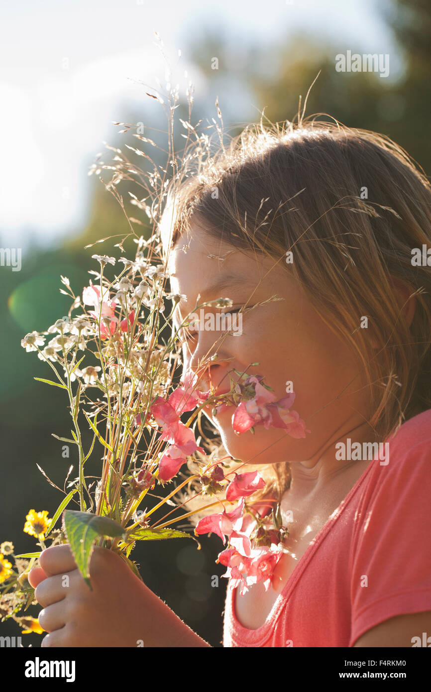 Girl (10-11) holding bunch of wild flowers - Stock Image