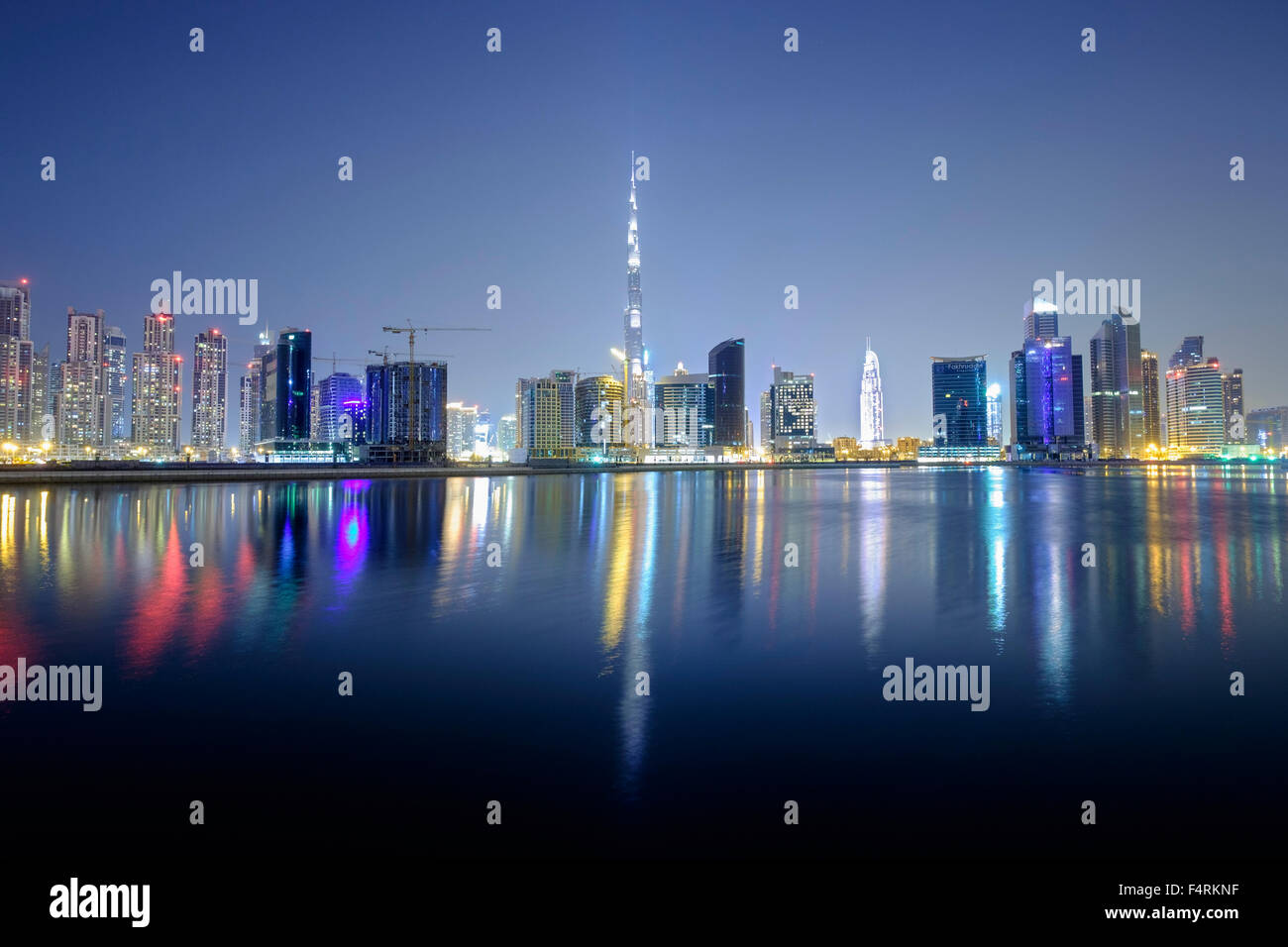 Night view of Burj Khalifa and Creek at new Business Bay district of  Dubai United Arab Emirates - Stock Image