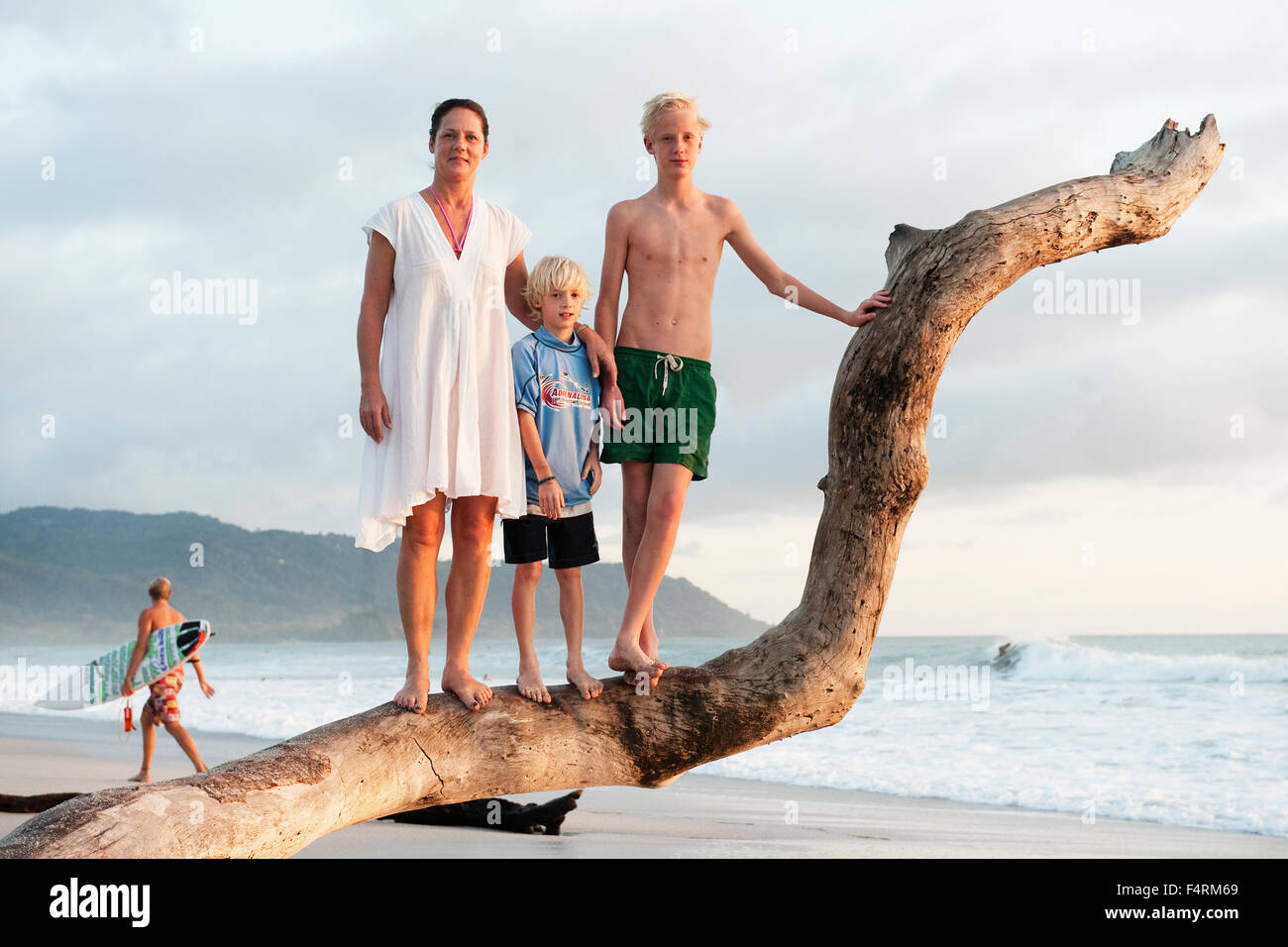 Costa Rica, Santa Teresa, Mother with two sons (10-11, 14-15) on beach - Stock Image