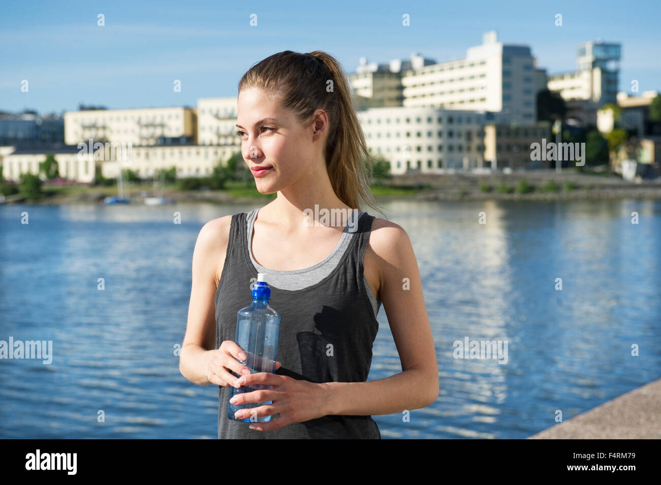 Young woman with water bottle, Hammarby Sjostad, Stockholm, Sweden in background - Stock Image