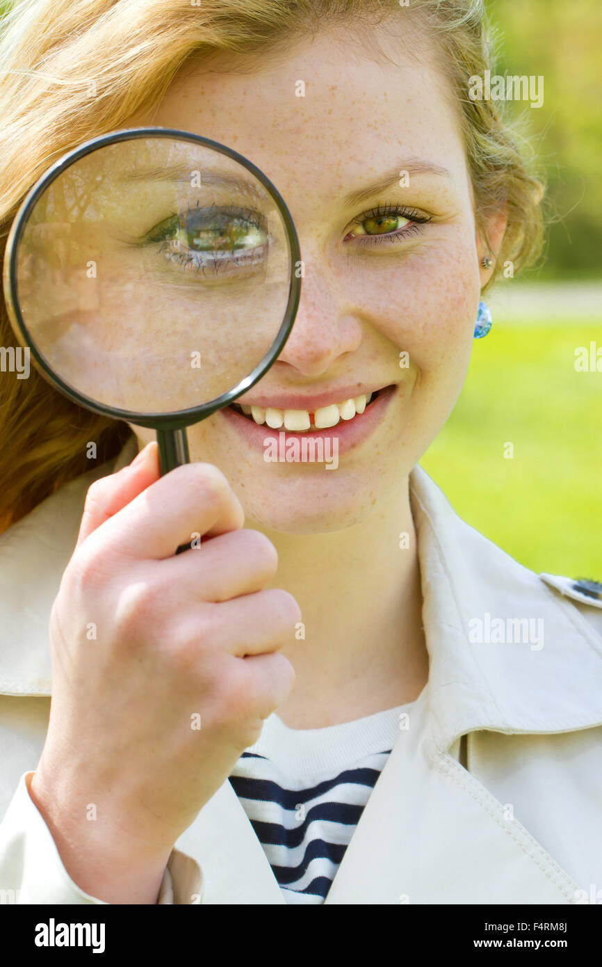 Young woman with magnifying glass - Stock Image