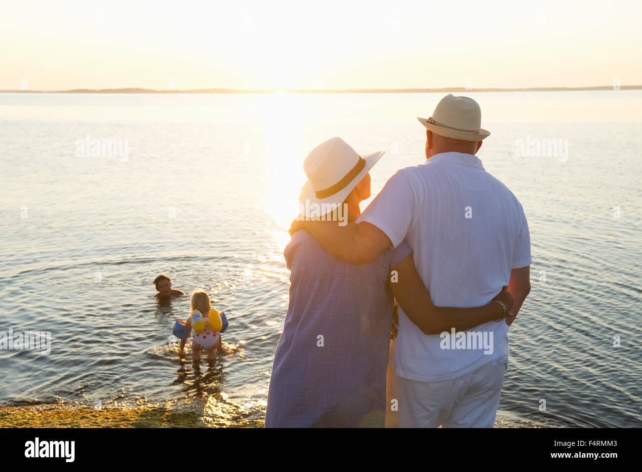 Rear view of mature couple with swimming children (4-5, 14-15) on background - Stock Image