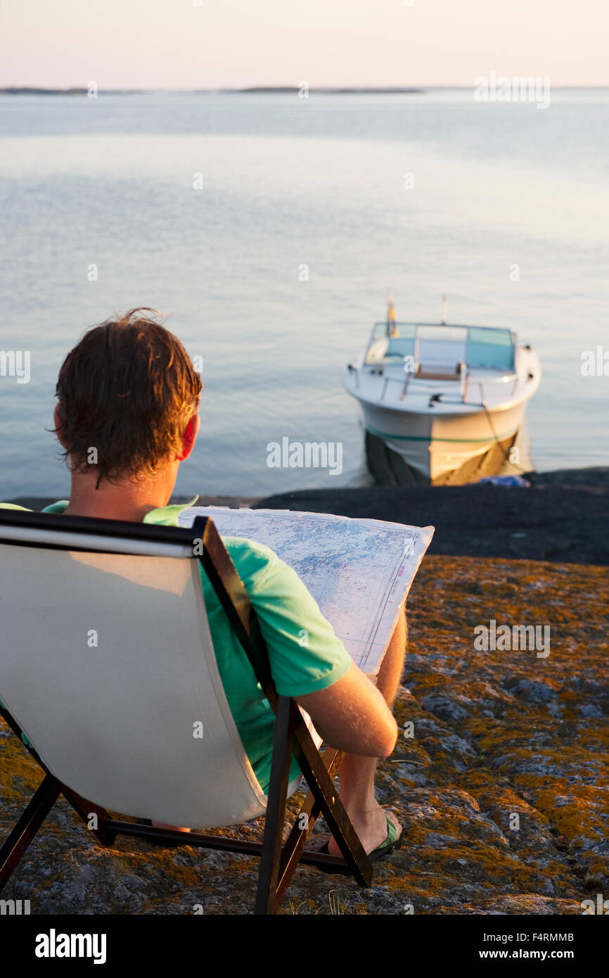 Sweden, Sodermanland, Stockholm Archipelago, Varmdo, Rear view of mature man on lounge chair reading map on rocky - Stock Image