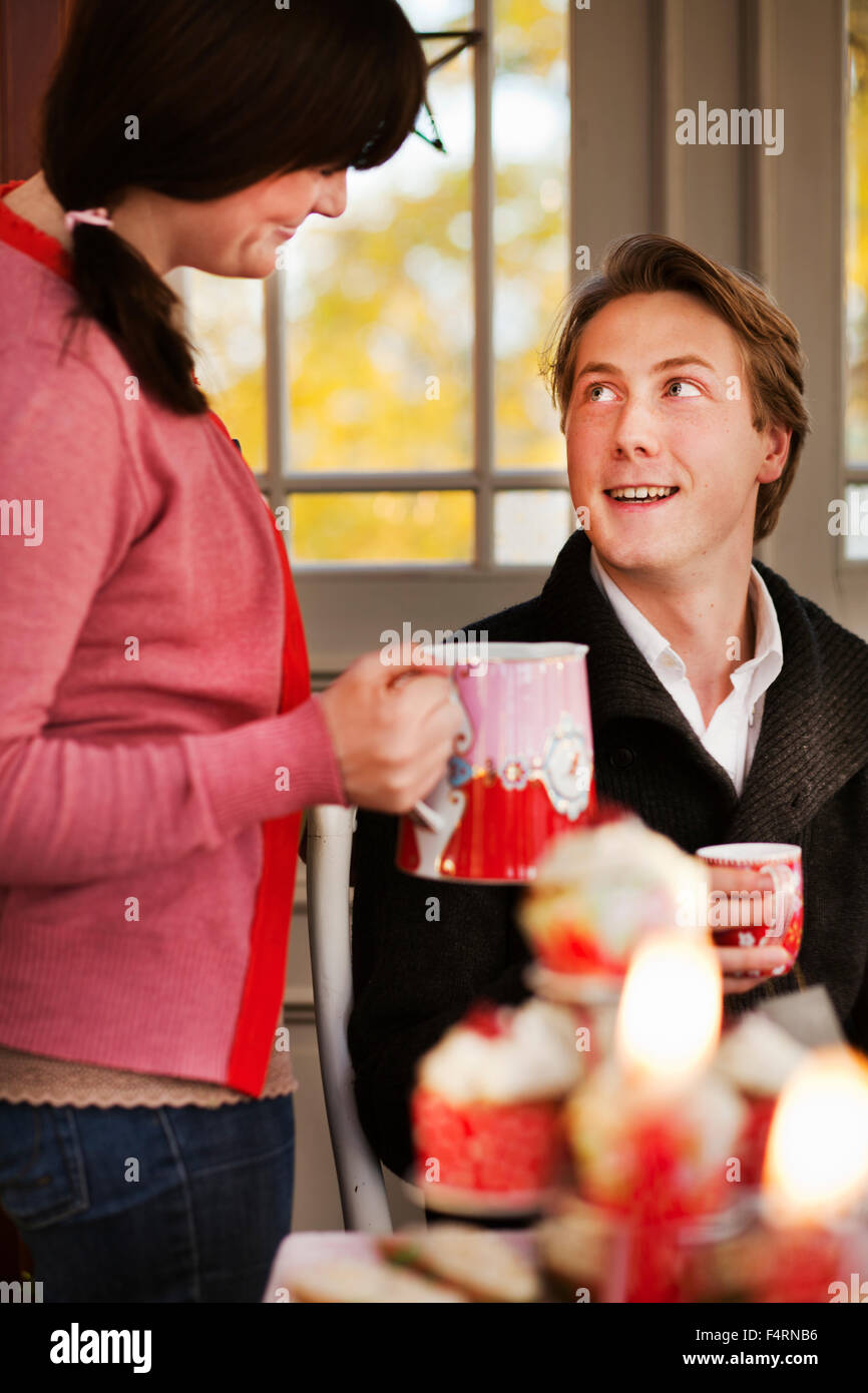 Woman offering mulled wine to man - Stock Image