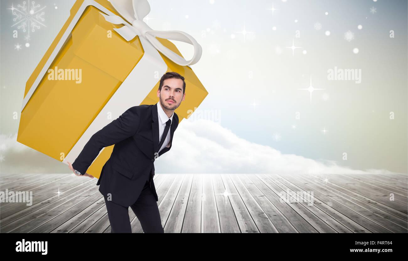 Composite image of stylish man with giant gift - Stock Image