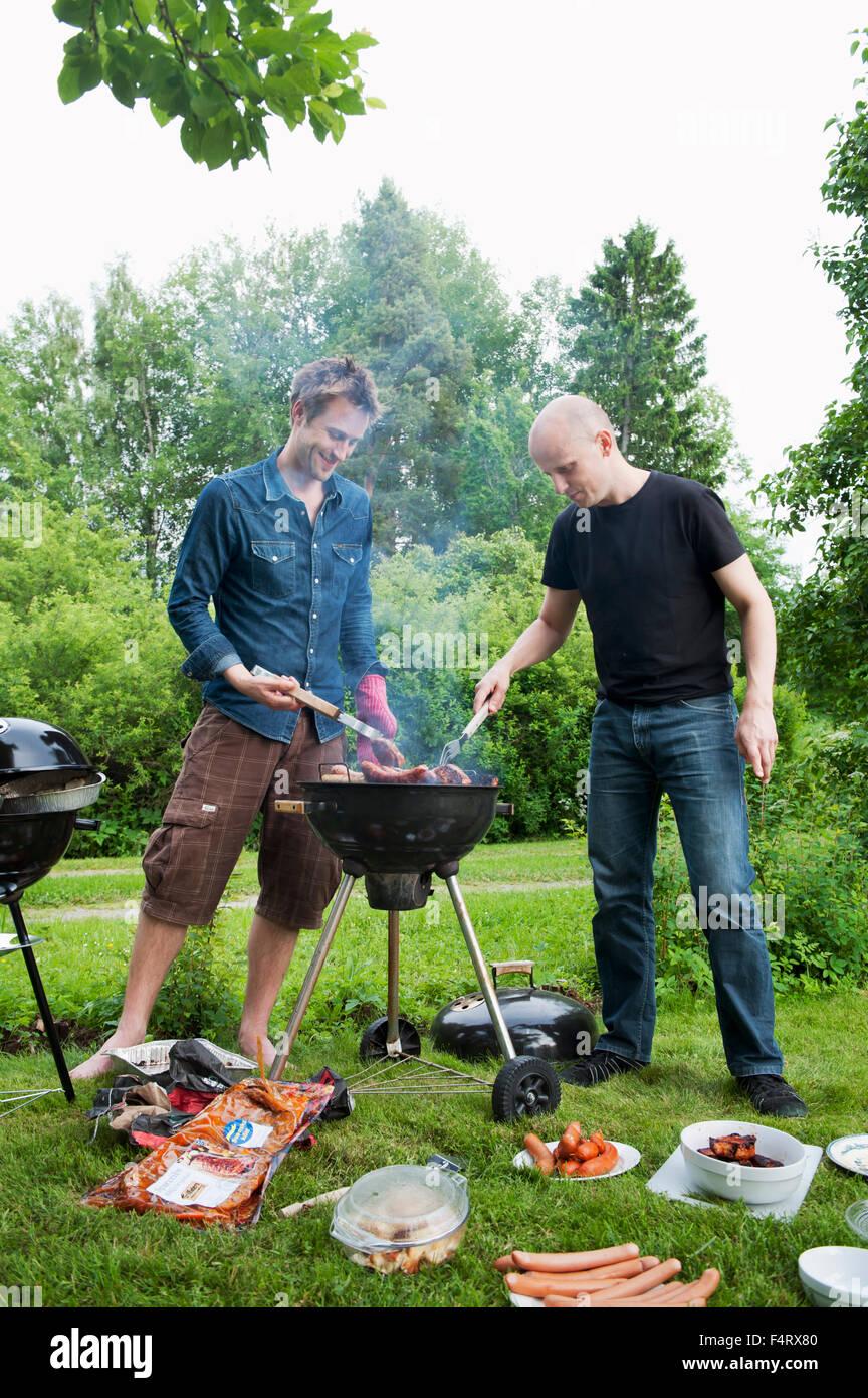 Sweden, Ostergotland, Vikbolandet, Mid-adult men having barbecue in backyard - Stock Image