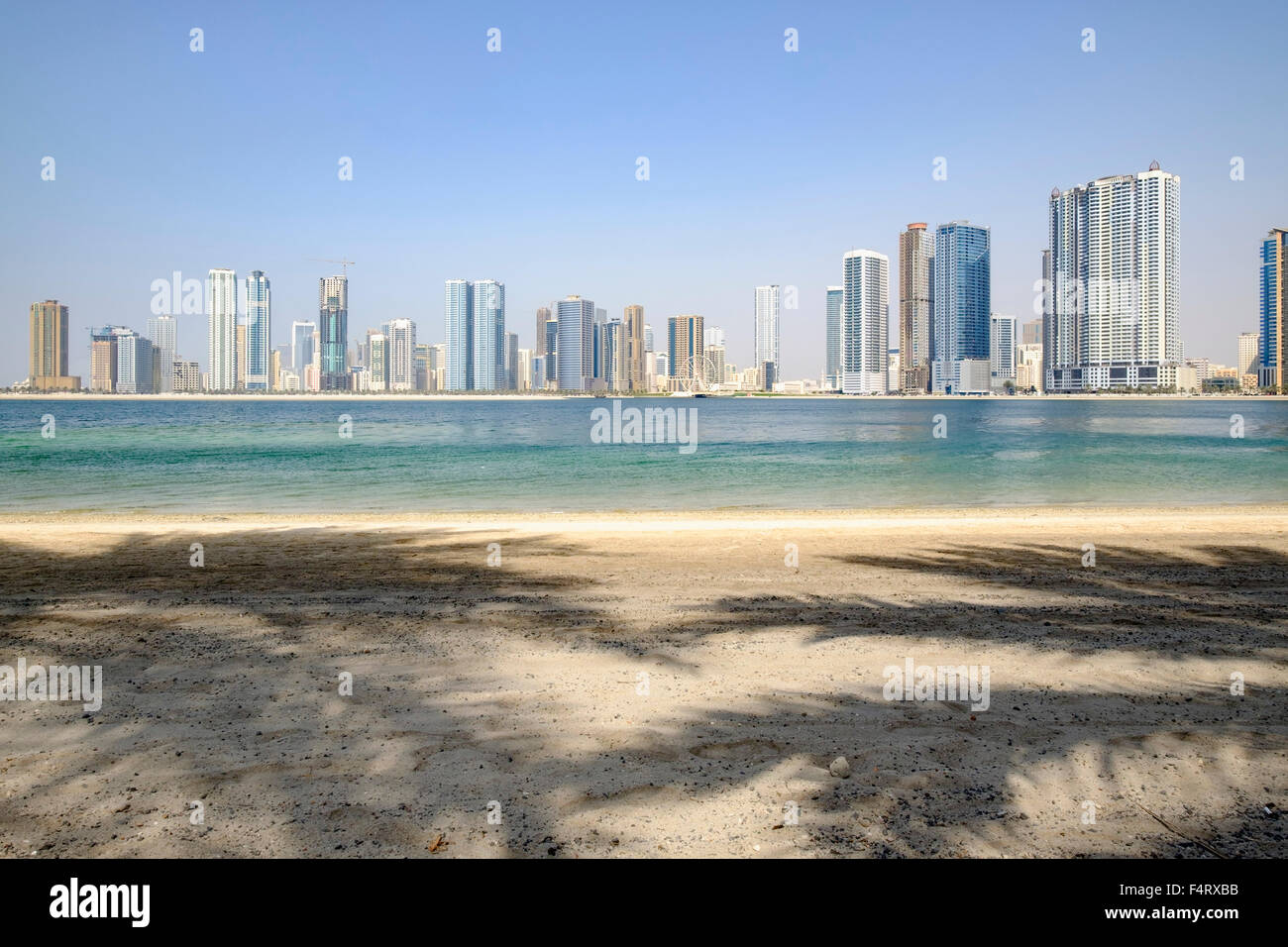 Daytime skyline view of beach and modern high-rise apartment buildings along Corniche in Sharjah United Arab Emirates - Stock Image
