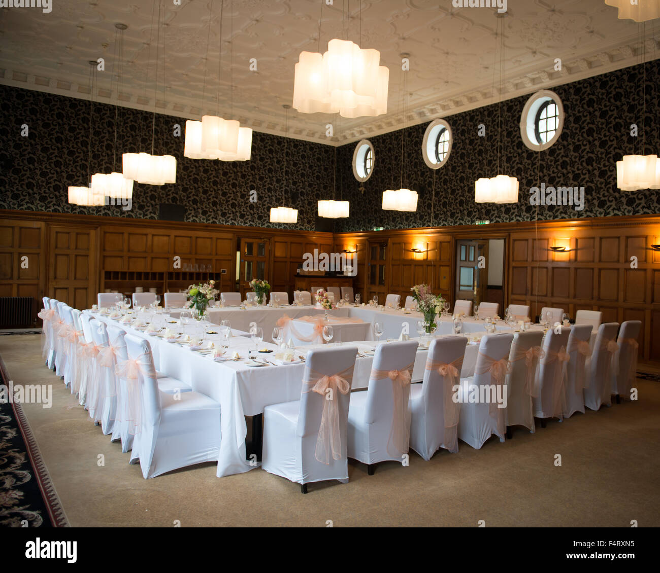 wedding reception room table layout tables set in a square formation with the cake in the centre white chair covers peach bows