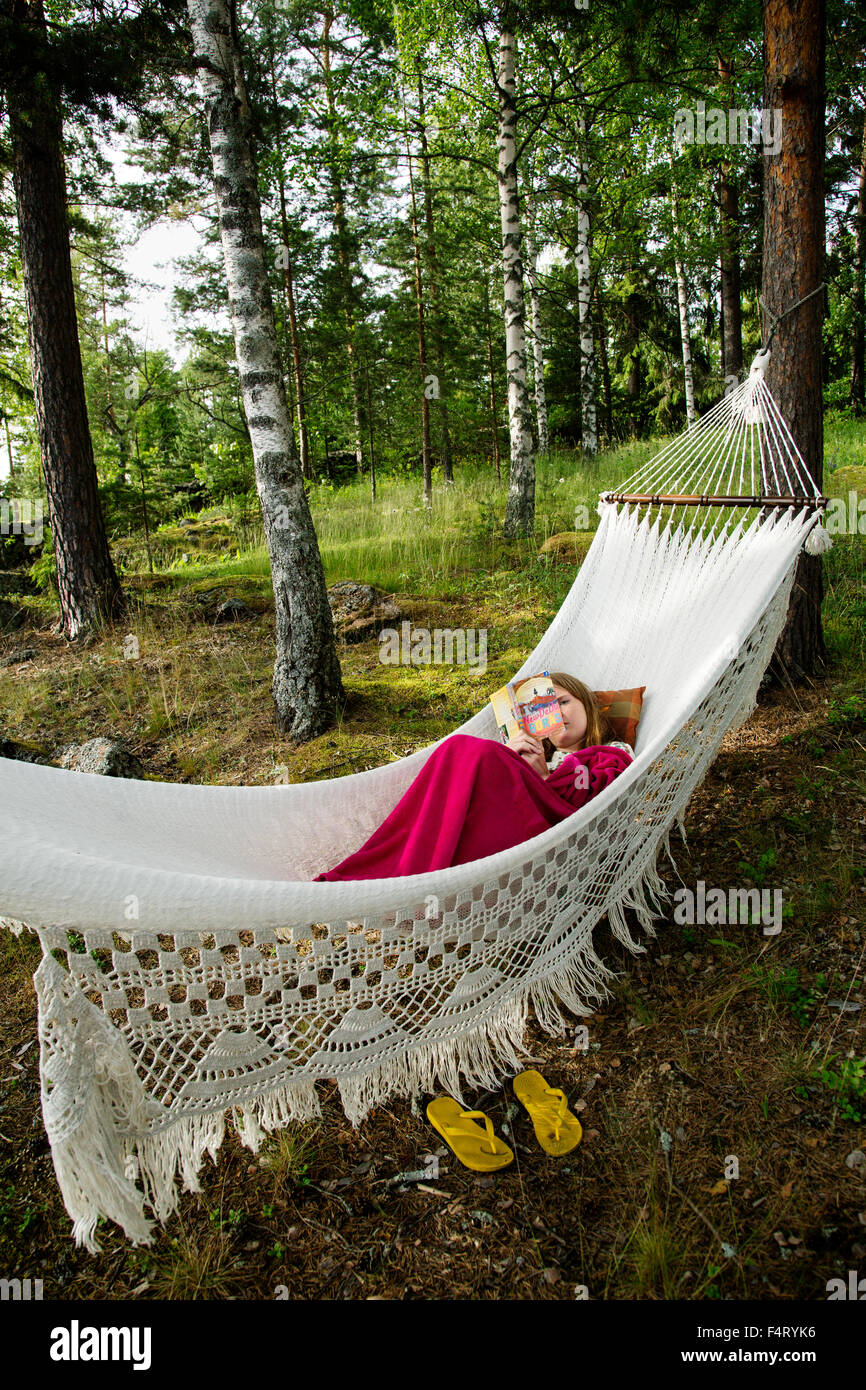 Sweden, Dalarna, Falun, Young woman lying on hammock and reading book - Stock Image