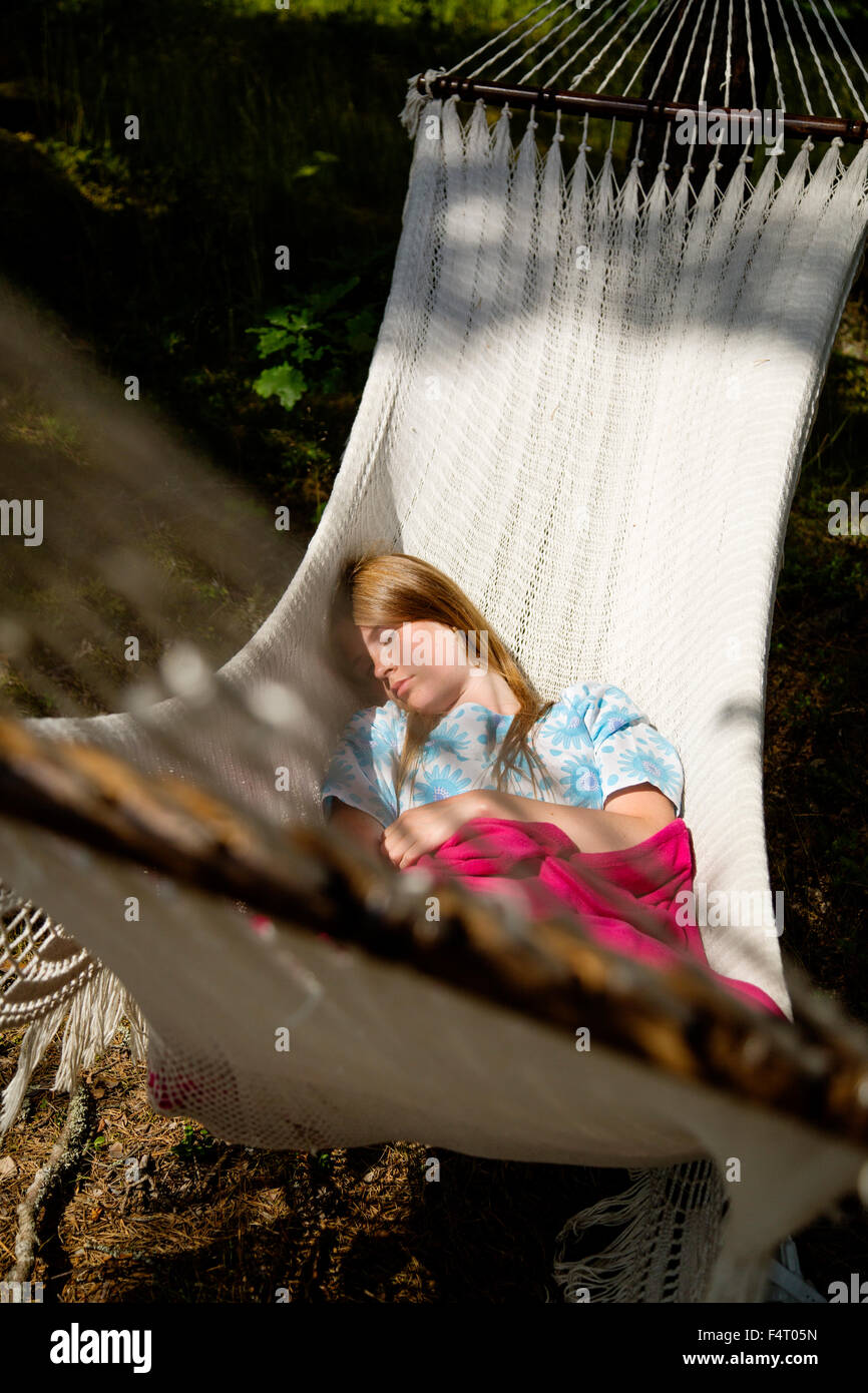 Sweden, Dalarna, Falun, Young woman lying on hammock in forest - Stock Image