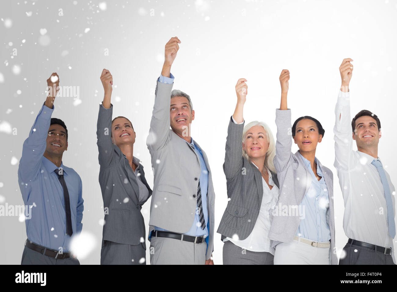 Composite image of smiling business people raising hands Stock Photo
