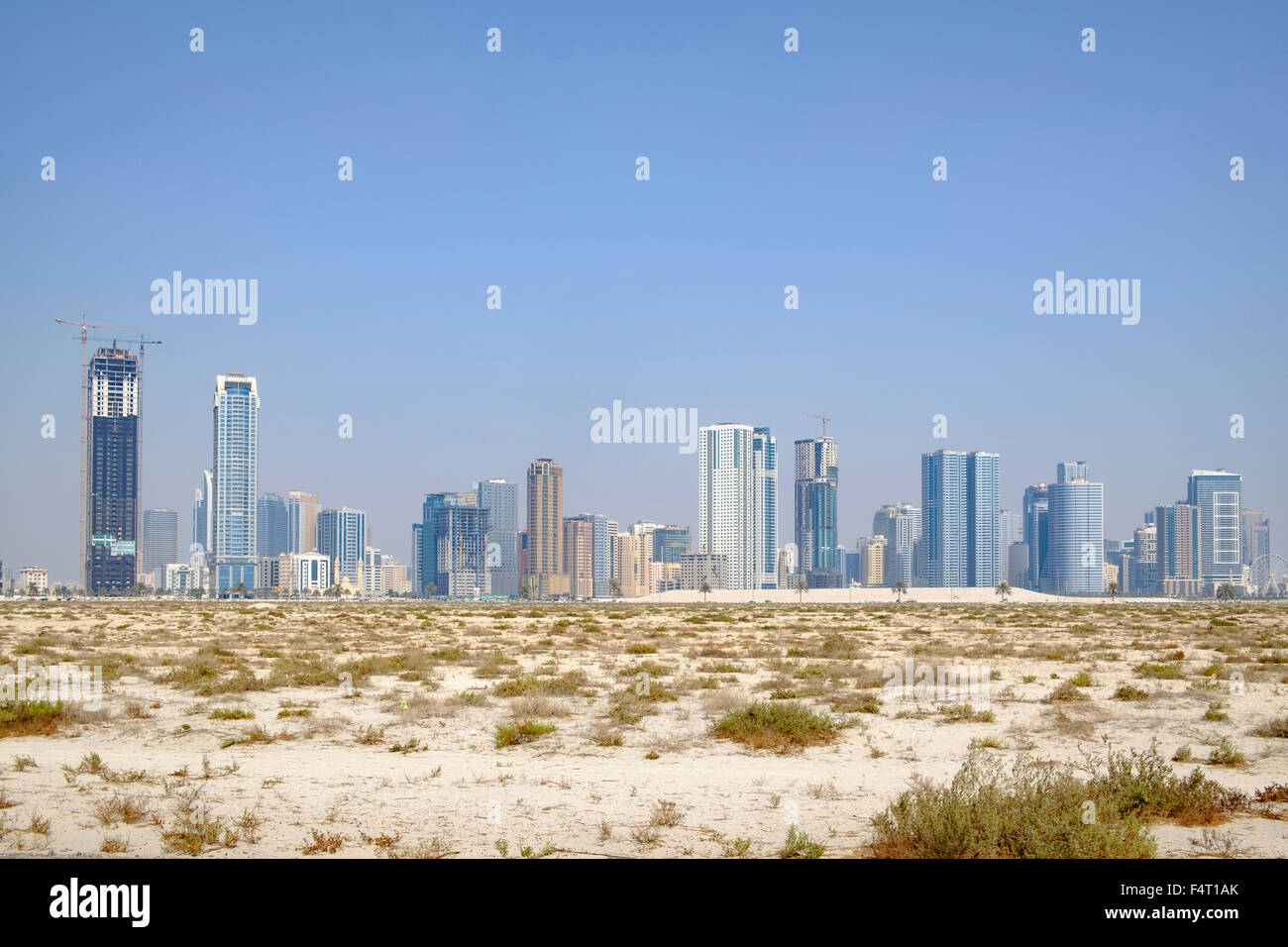 Daytime skyline view of  modern high-rise apartment buildings from desert  in Sharjah United Arab Emirates - Stock Image