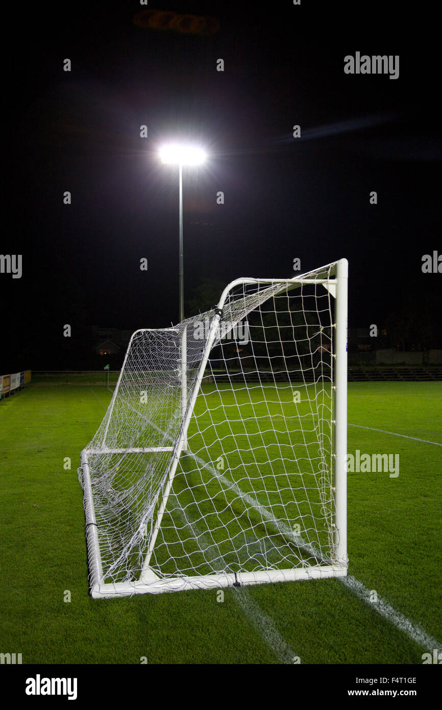 Goalposts on a football pitch with floodlight in background. - Stock Image