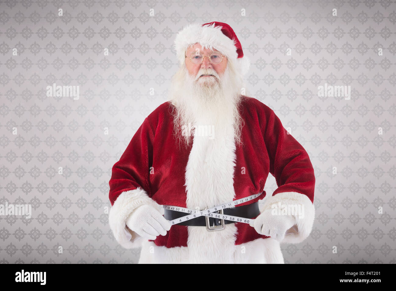 Composite image of santa claus measures his belly - Stock Image