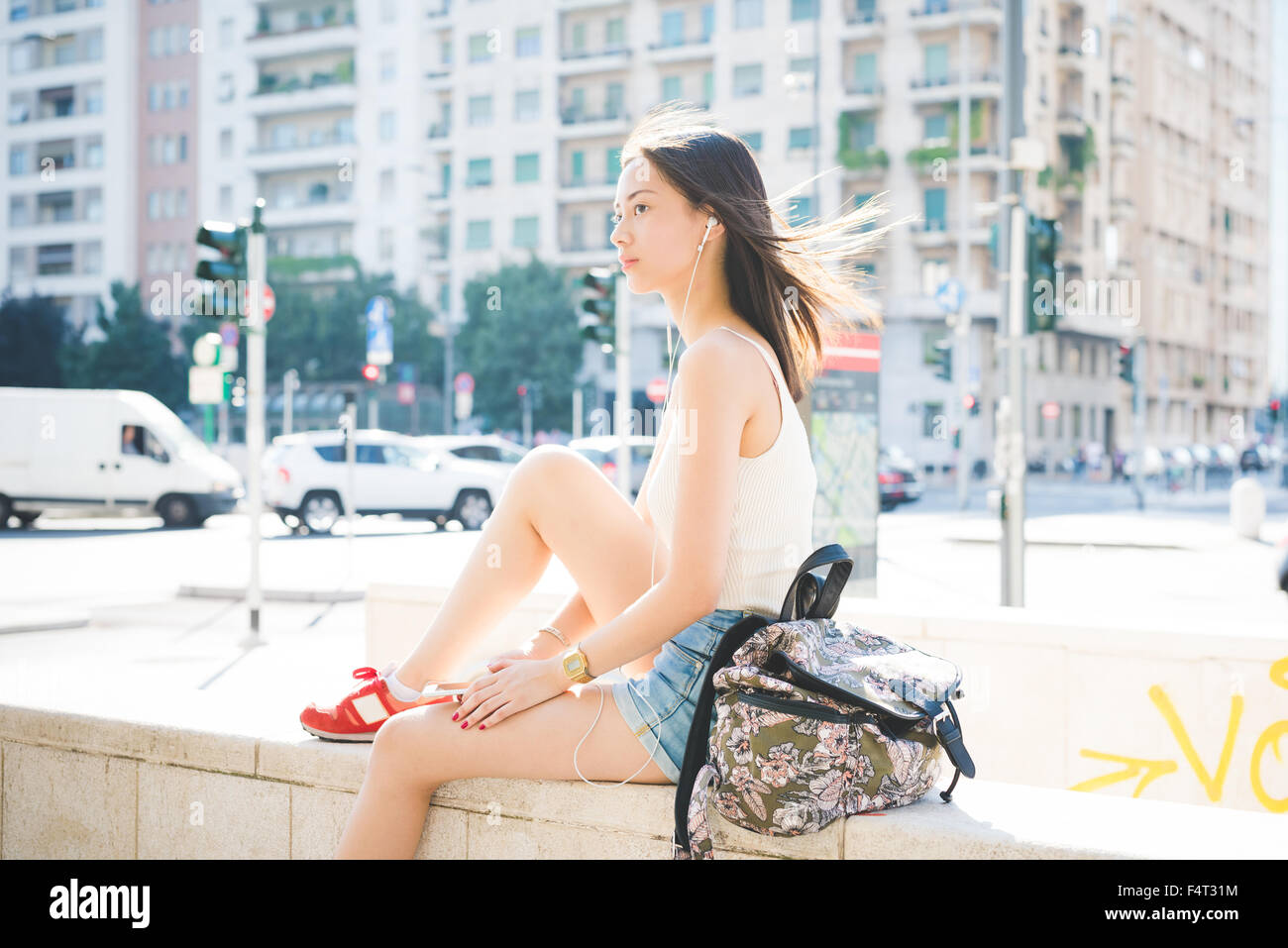 Young handsome asiatic long brown straight hair woman sitting on a small wall listening music with earphones, overlooking - Stock Image
