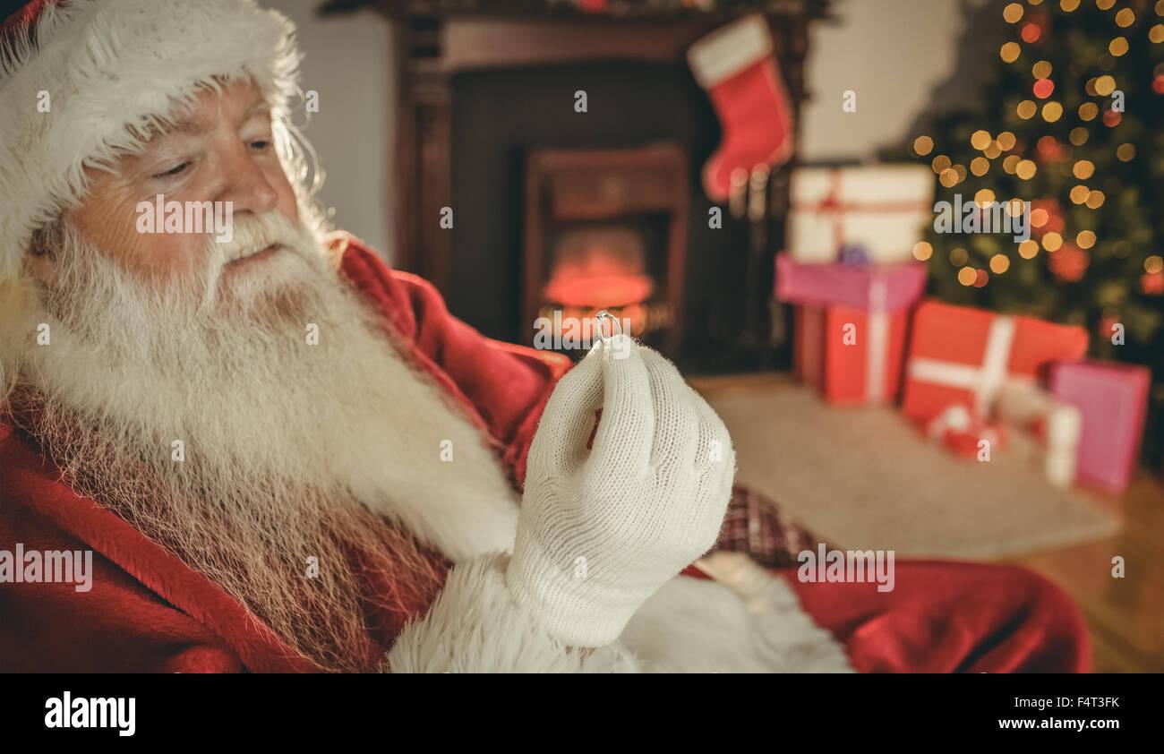 Santa claus holding engagement ring - Stock Image