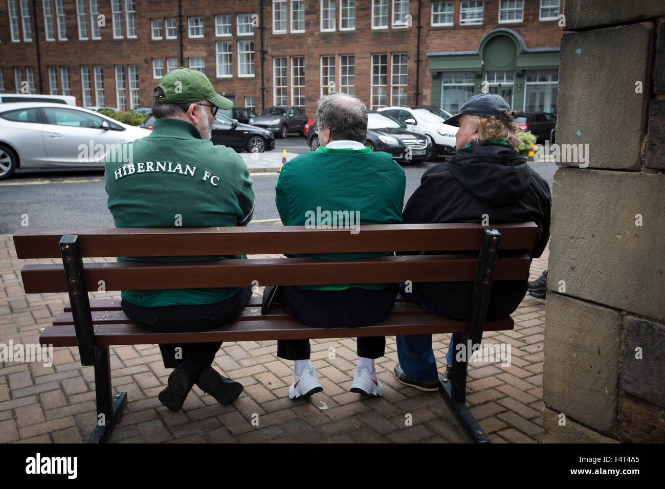 Three home fans sitting on a bench outside the West Stand at Easter Road stadium before the Scottish Championship - Stock Image