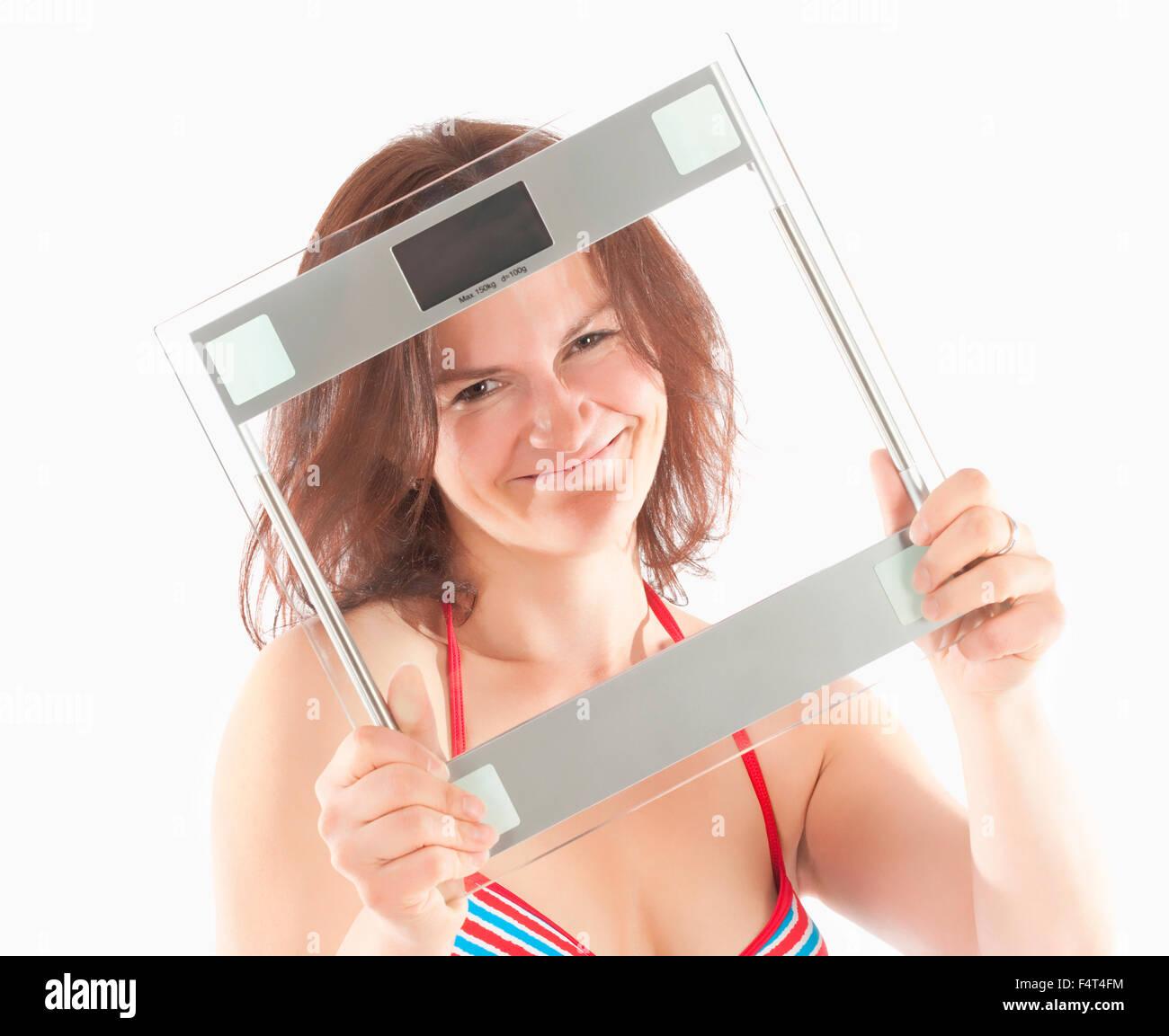 Woman in Bikini Swimwear Holding Scale - Stock Image