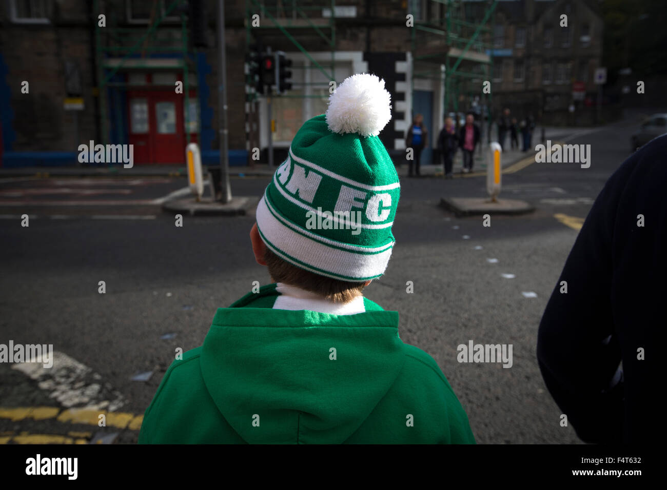 A young home supporter in a bobble hat making his way from Easter Road stadium at the conclusion of the Scottish - Stock Image