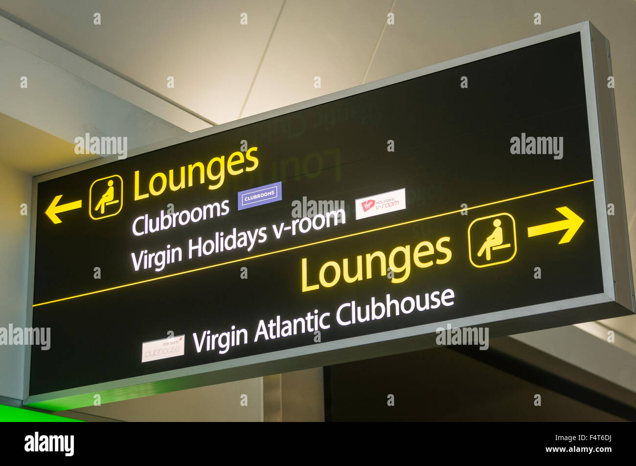 Signs giving the directions to airport lounges, including the Virgin Holidays v-room and Atlantic Clubhouse - Stock Image