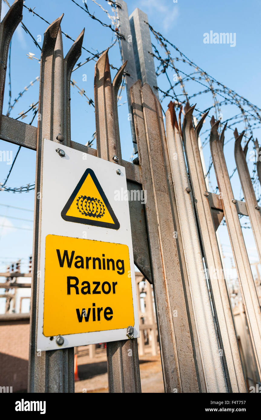 Warning sign on a fence to an electricity power substation warning of the existence of razor wire. - Stock Image