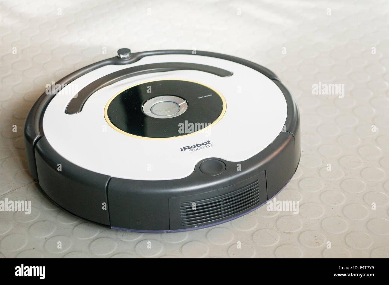 An iRobot Roomba robotic vacuum cleaner cleaning a rubber vinyl kitchen floor - Stock Image