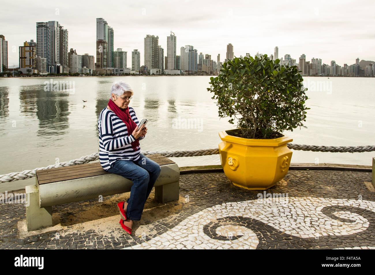 Elderly woman on the cell phone sitting on a bench at Pontal da Barra Sul. Balneario Camboriu, Santa Catarina, Brazil. - Stock Image