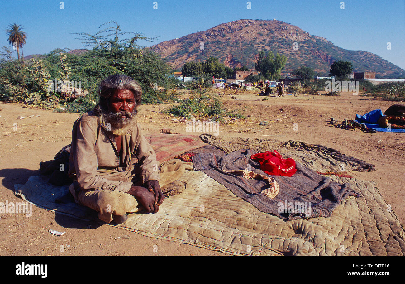 Man belonging to a nomadic group. He is sitting in front of his bed ( Rajasthan, India) - Stock Image