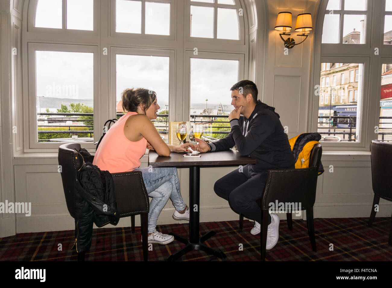 Young couple holding hands having serious relaxed conversation at pub in Argyll Hotel, Dunoon, Scotland.   ©Myrleen - Stock Image