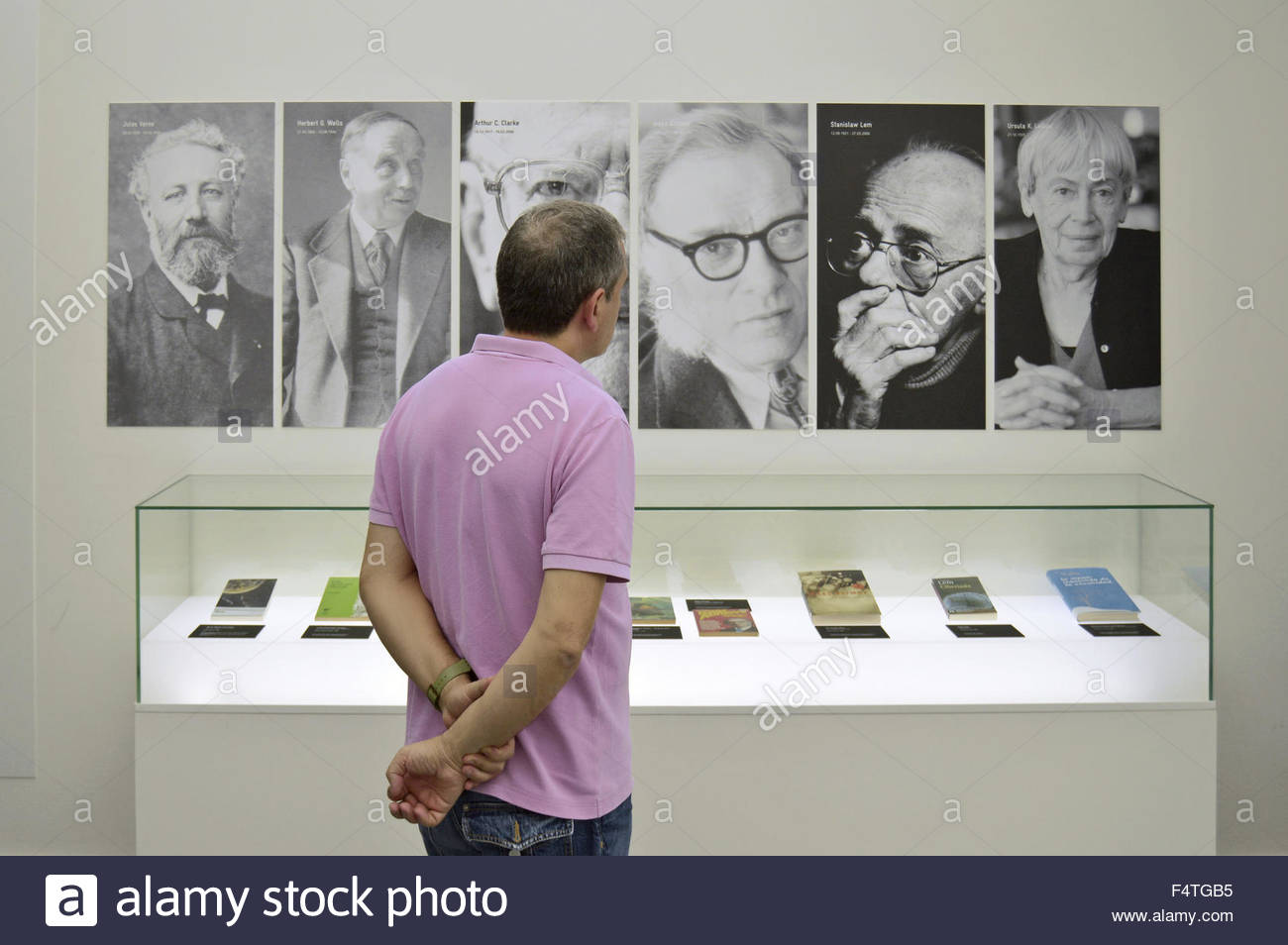 Visitor standing in front of the wall with portraits of famous science-fiction writers at ObraCaixa (science) museum - Stock Image