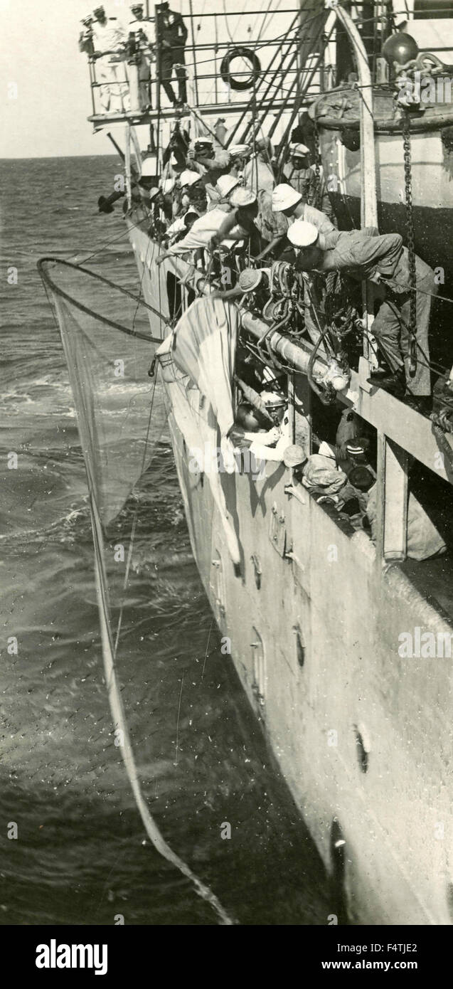 Group of sailors retrieve an object from a ship - Stock Image