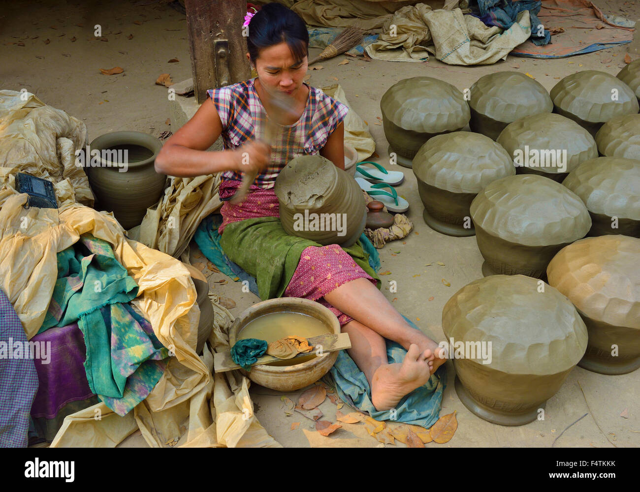 Woman in the irrawaddy Yandabo village  near Mandalay beating out clay waterpots  into shape with  a wooden paddle - Stock Image