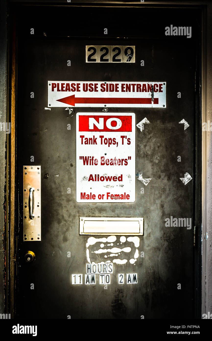 Dress code posted on funky beat-up door of dive bar, 'No tank tops, T's or wife beaters allowed Male or - Stock Image