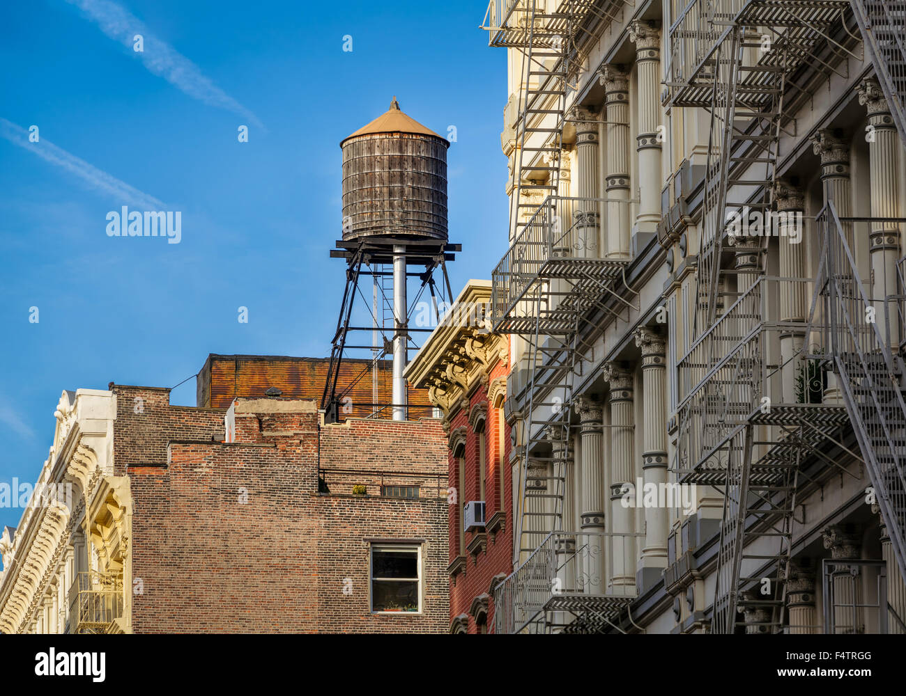 Wooden water tank and cast iron facade buildings with fire escapes, Soho, Downtown Manhattan, New York City - Stock Image