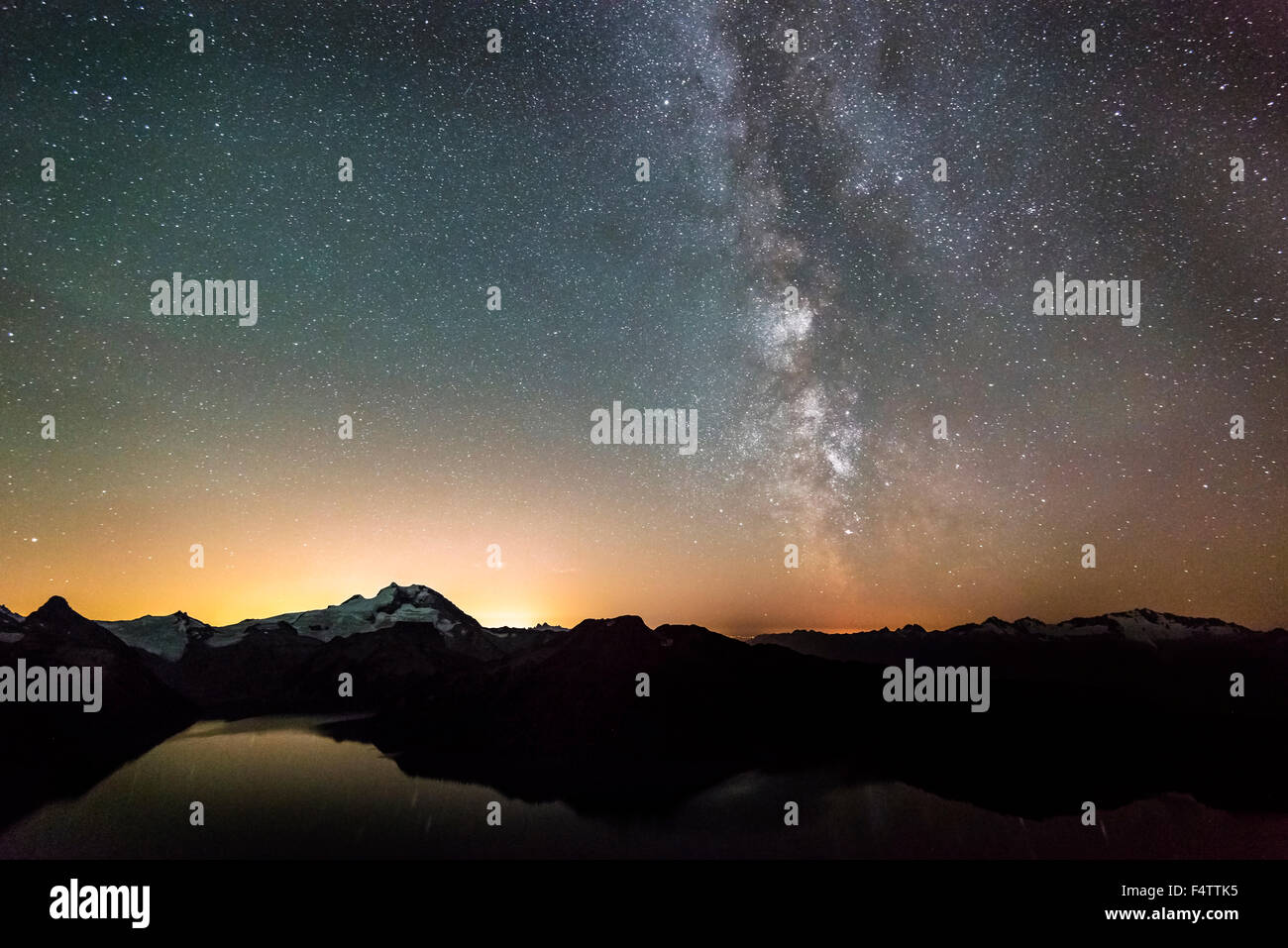 The Milky Way and light pollution from Vancouver looking over Garibaldi Lake, Whistler, BC, Canada. - Stock Image