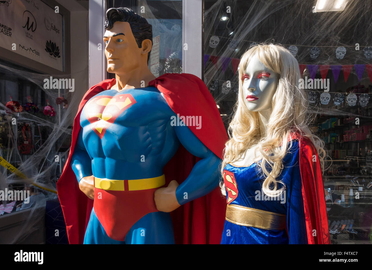 Life-size plastic statues of Superman and Supergirl outside a specialty store - Stock Image