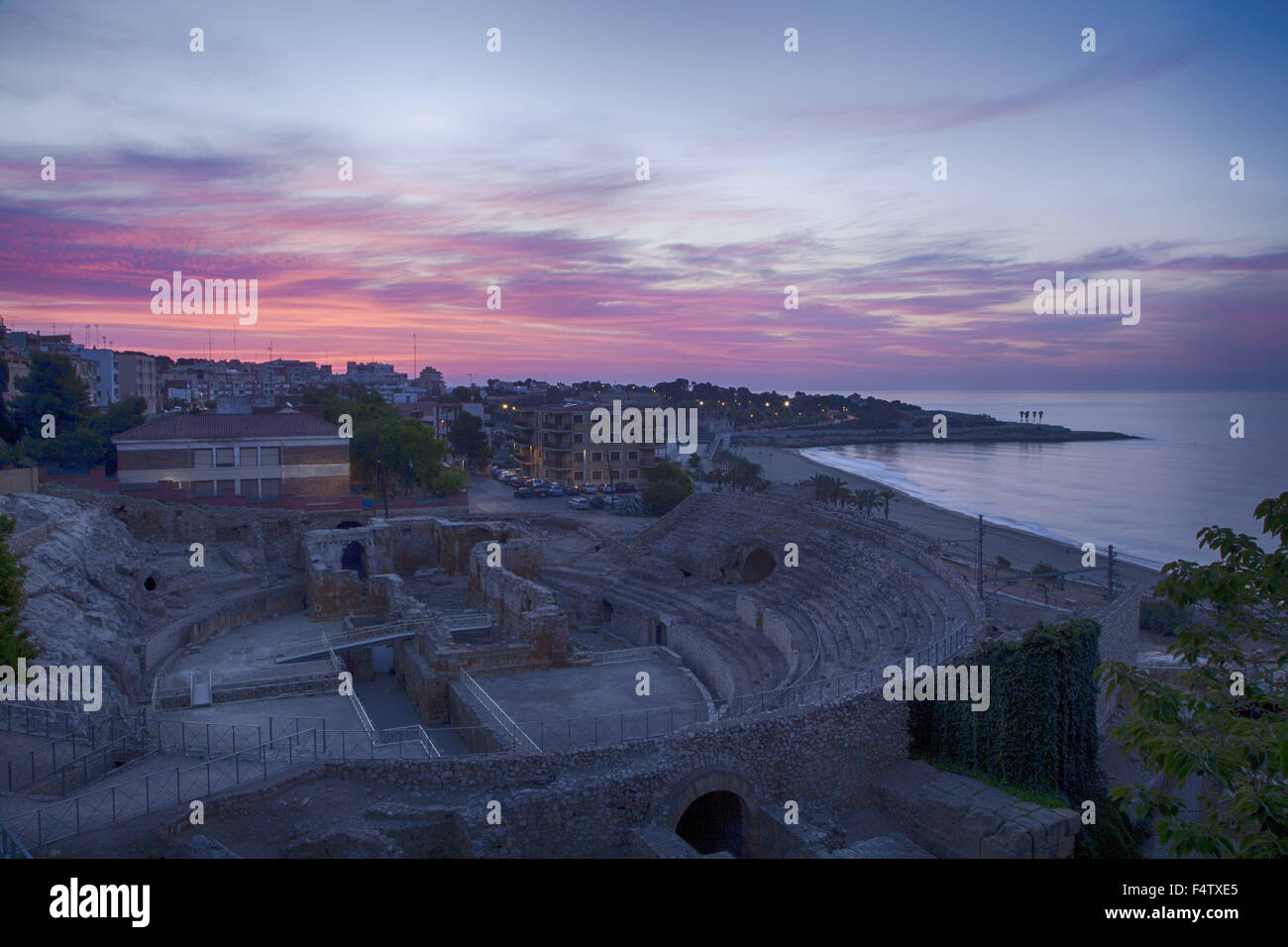 Sunrise from the high viewpoint over the historic Roman amphitheater, the UNESCO site in Tarragona Valencia Spain. - Stock Image