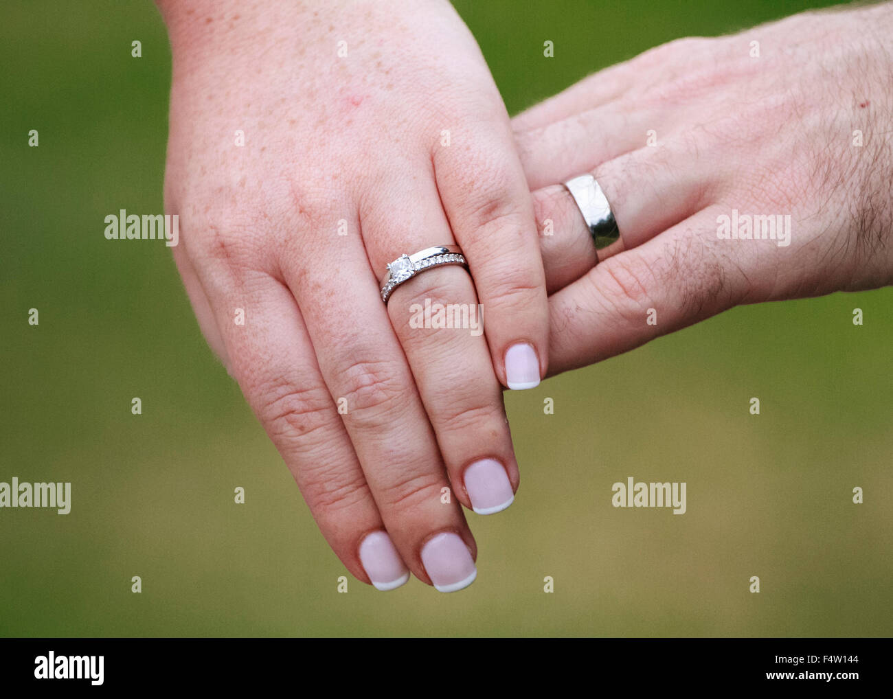Close-up hands of newly married couple showing their wedding rings ...
