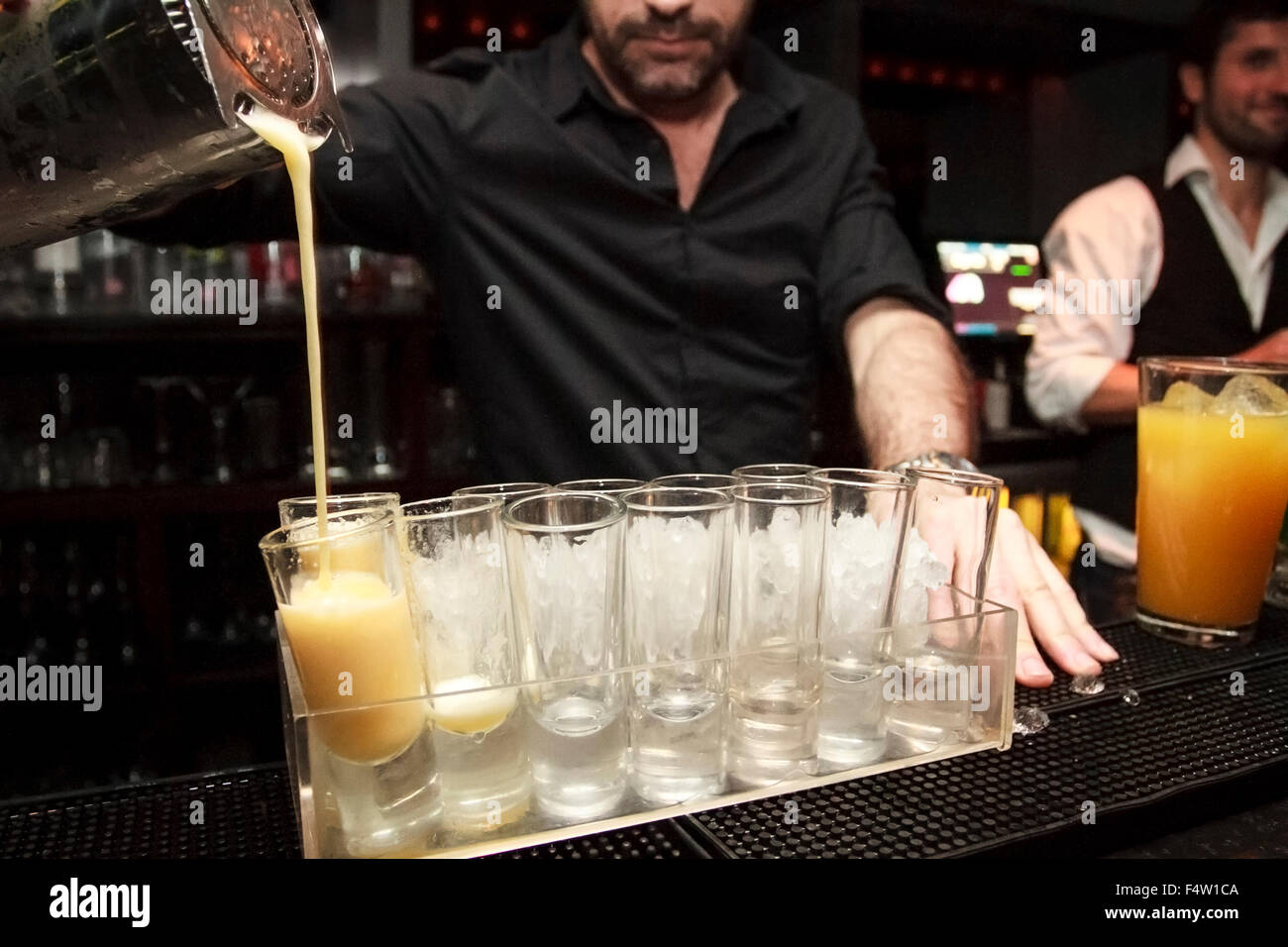 Bartender pouring cocktail shots on a tray full of shot glasses - Stock Image