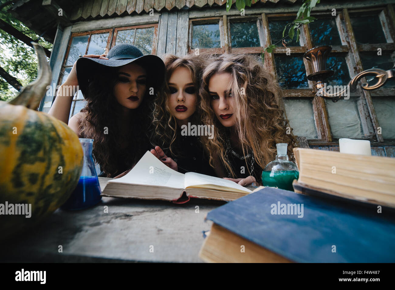 Three vintage witches perform magic ritual, at the table, reading a