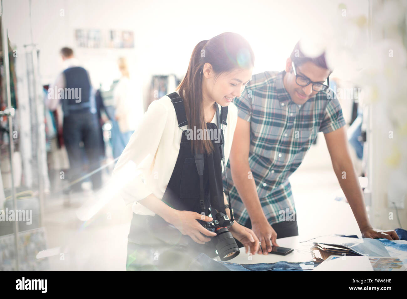 Photographer and fashion designer viewing proofs in sunny office - Stock Image