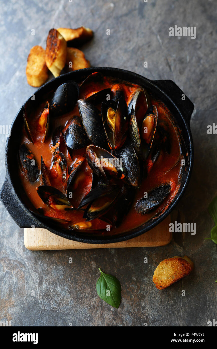 mussels in red sauce in pan - Stock Image