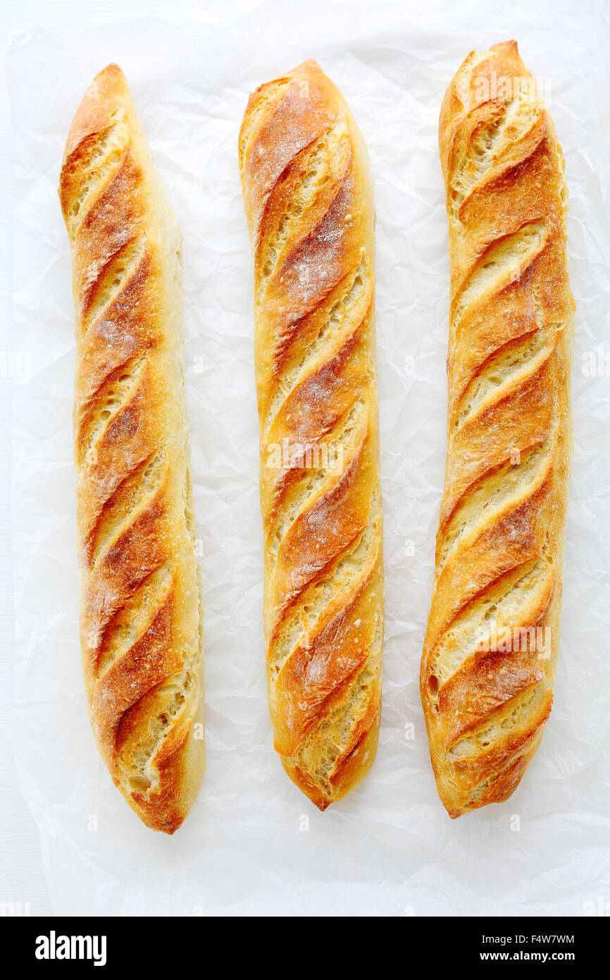 fresh baguette on white paper, top view Stock Photo