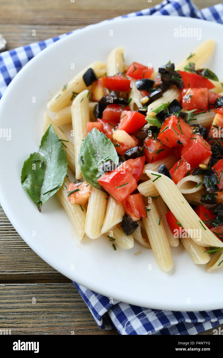 penne with tomato and olive sauce on plate - Stock Image