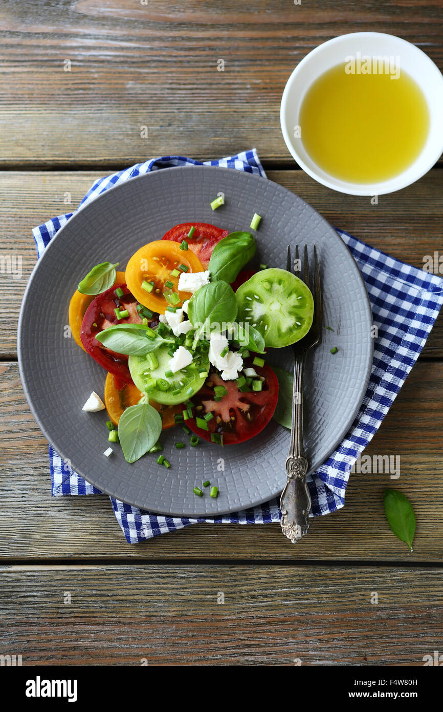 tomatoes salad with soft cheese, food top view - Stock Image