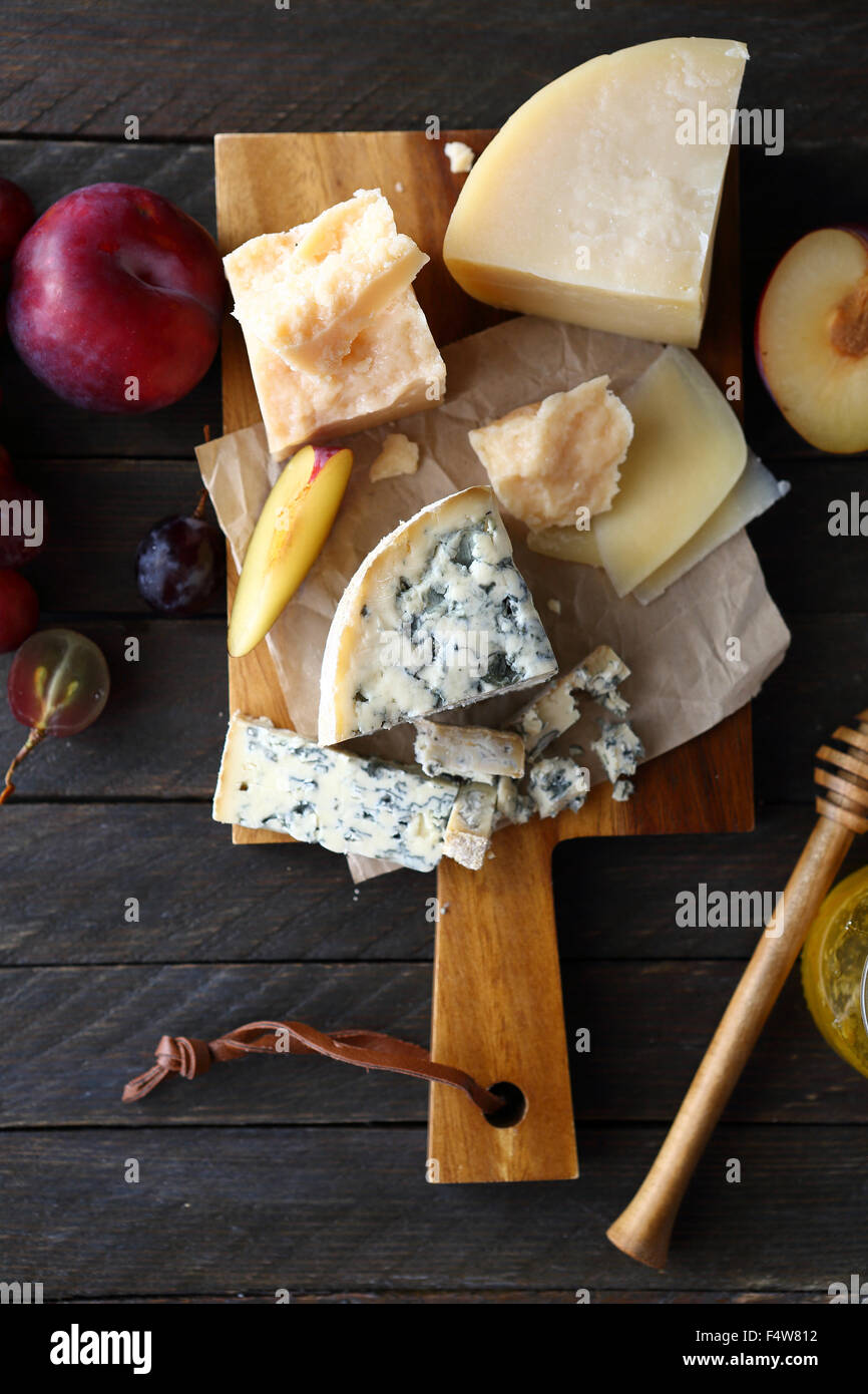 mix cheeses on cutting board, food top view - Stock Image