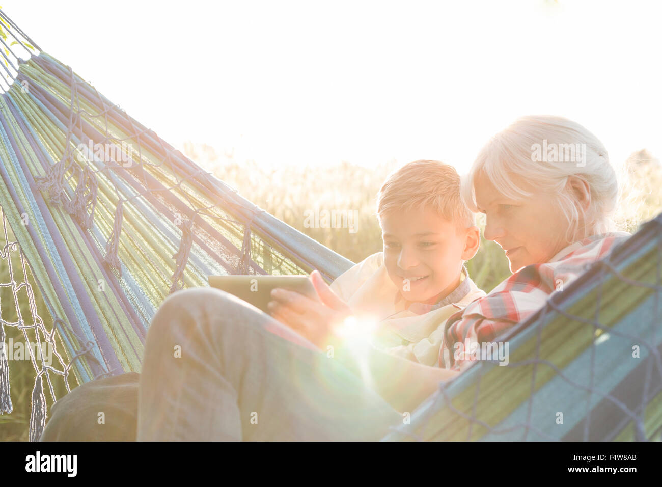 Grandmother and grandson using digital tablet in sunny hammock - Stock Image
